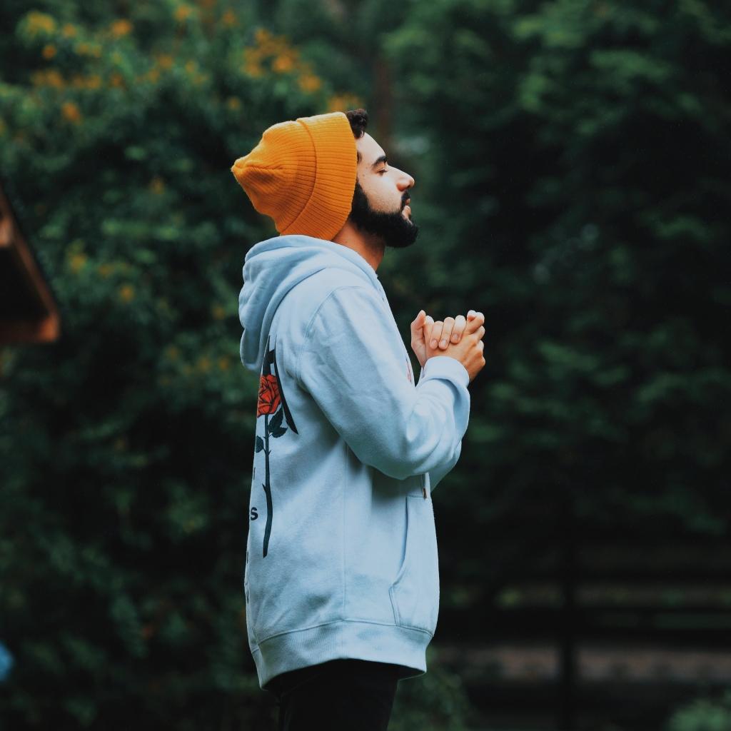 man in sweatshirt and beanie eyes closed praying