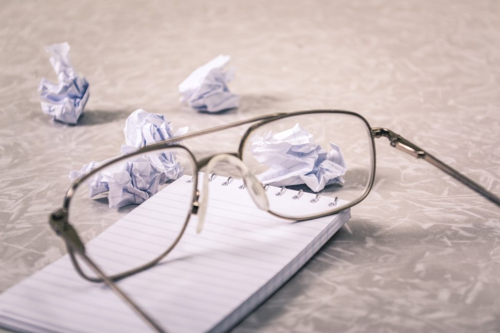 eyeglasses and crumpled paper